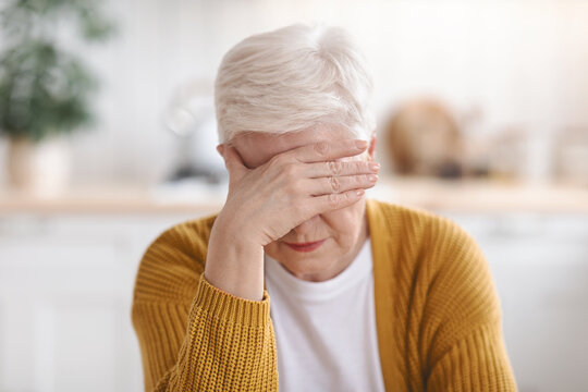 Senior woman suffering from migraine, kitchen interior