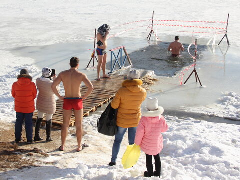 Winter ice swimming sport, a European people stand on snowy shore near ice hole water with swimmer man on a Sunny frosty winter day, healthy lifestyle