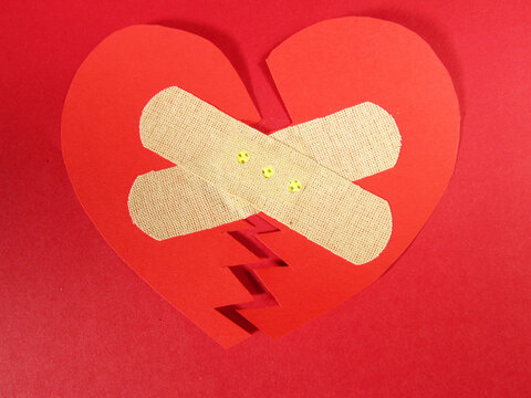 Red broken bandaged heart on red background.