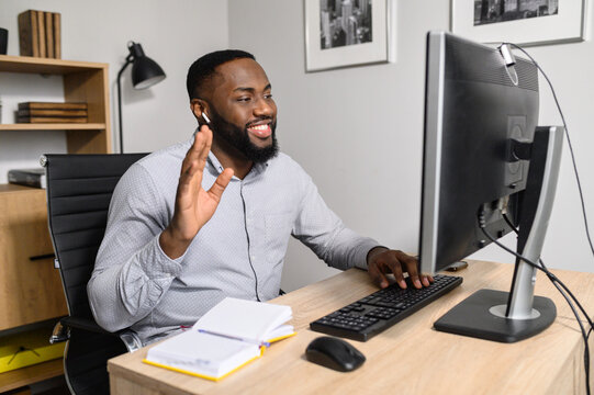 A positive multiracial coach, mentor conducts online webinar, he is waving hand into webcam. An African-American guy is using PC for online conversation via video call
