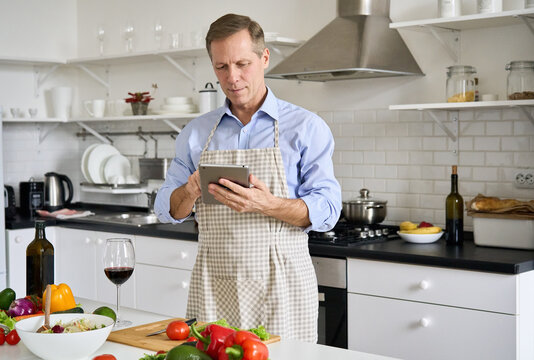 Old senior 50s man wearing apron using tablet preparing vegetable salad in kitchen. Middle aged chef searching recipes, ordering food online, watching cooking videos preparing healthy food at home.