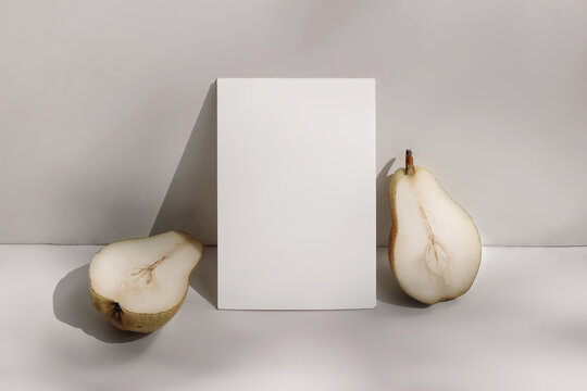 Trendy summer stationery still life scene. Closeup of cut pear fruit on beige table background in sunlight. Blank paper card, invitation mockup scene lean on champagne wall, long shadows.