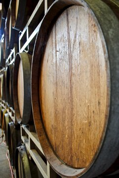 Stacked wooden wine barrels or cask. Selective focus with blurred distance. Room for text. Wood barrel heads and chime, the beveled edge at the end of each stave.