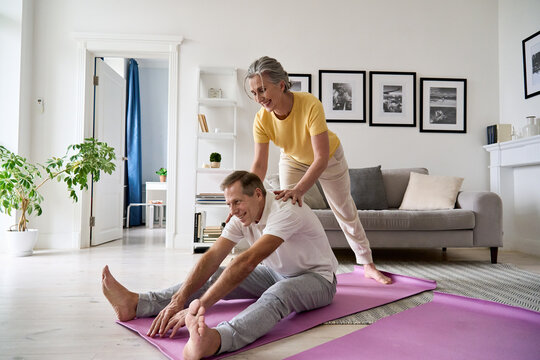Fit active retired middle aged wife helping senior husband doing stretching exercise at home. Happy healthy older senior 60s couple enjoying fitness sport training workout together in apartment.
