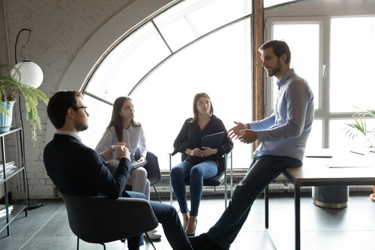 Confident businessman leading briefing, training diverse employees at meeting, colleagues sitting in circle listening to mentor coach, business partners coworkers discussing project strategy
