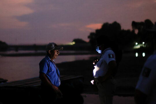 An immigration agent asks questions to a man after he crossed the Suchiate River, while guarding the border to prevent a migrant caravan of Central Americans from entering, in Ciudad Hidalgo