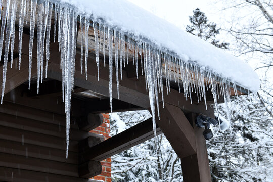 Icicles hanging off log cabin roof from melting snow after storm