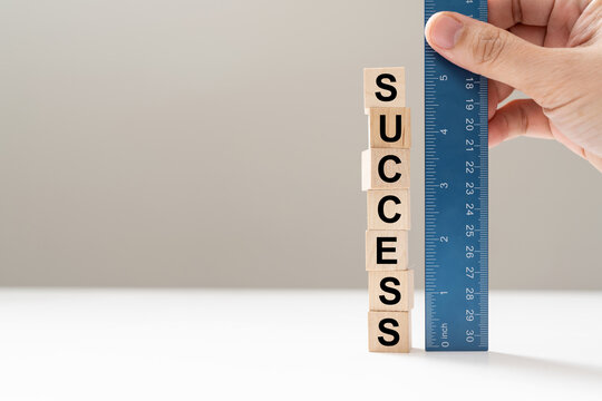 Measure success word using blue ruler, representing a review, evaluation or assessment of an employee