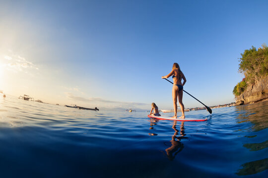 Active paddle boarder at sunset sea. Young mother with little clild paddling on stand up paddleboard. Healthy lifestyle. Water sport, SUP surfing tour in adventure camp on family summer beach vacation