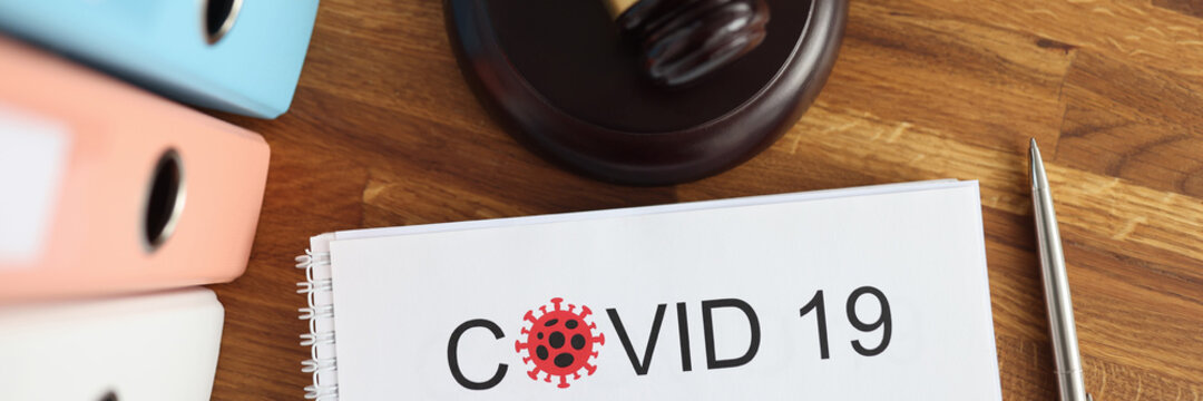 On the table is a judge's wooden gavel and document with the inscription covid -19. Coronavirus pandemic litigation concept