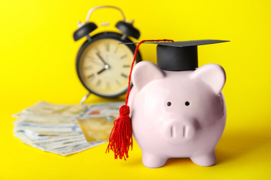 Piggy bank with graduation hat, money and alarm clock on color background