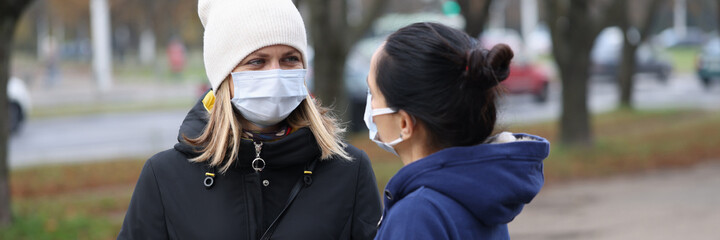 Two young women communicating in protective face masks outside. Safety rules during the covid-19...