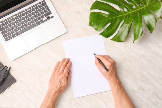Male hands with blank paper sheet and laptop on light background