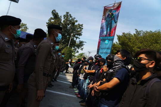Volunteer guards of the anti-government protest movement stand guard in front of police officers at the Khlong Luang police station in Pathum Thani province