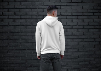 Long sleeve white mens clothing template on young guy on brick wall background, back view, blank...