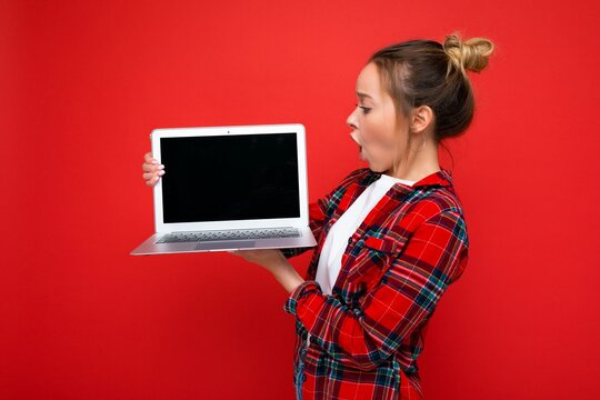 side profile photo of Beautiful shocked amazed young woman holding laptop wearing red shirt looking at monitor display isolated on red background