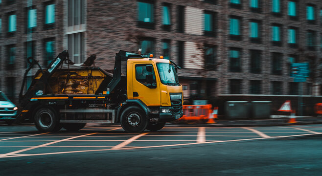Panning shot of a yellow dumpster truck taking a turn in an english city of Cambridge. Background blurred with low shutter speed