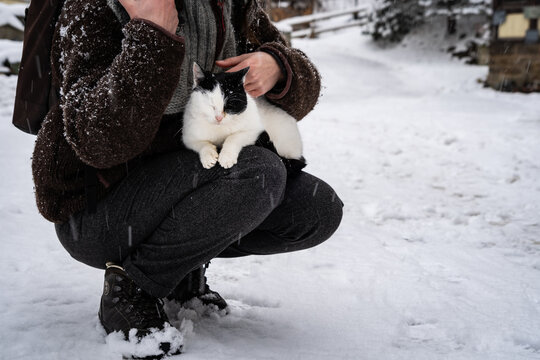 A black and white cat sitting on a woman's lap outside on a snowy day