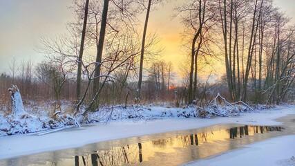zimowy krajobraz częściowo zamarzniętej rzeki koło Włodawy dużo śniegu niebieskie niebo złota godzina
