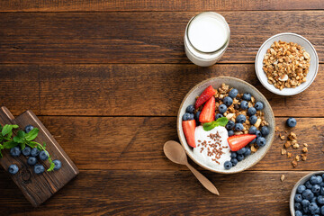 Granola bowl with berries and greek yogurt on a rustic wooden table background, top view