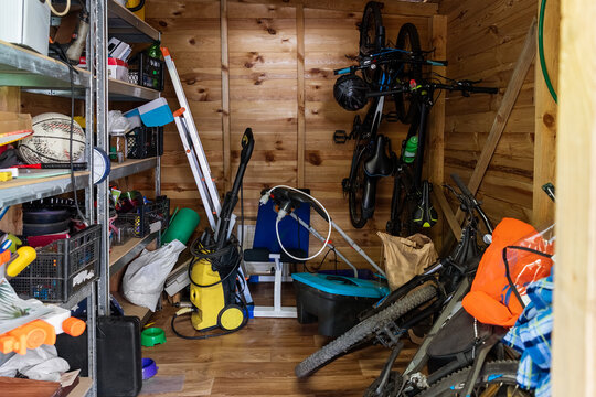 Suburban home wooden storage utility unit shed with miscellaneous stuff on shelves, bikes, exercise machine, ladder, garden tools and equipment. Messy and chaos at house yard barn. Organization order