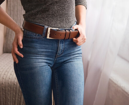 Elegant, leather, brown belt on a belt with a metal buckle for a girl. Original handmade leather clothing accessory