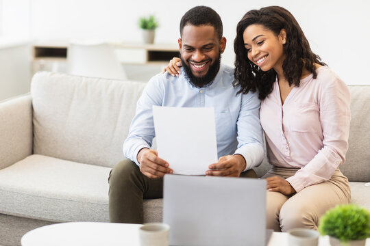 Positive black couple reading letter at home, sitting on couch