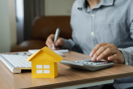 Business  Finance concept. Close up yellow paper house model with young Asian man wear grey shirt ongoing to calculate home loan mortgage to summary expense payment  with using laptop on office deck