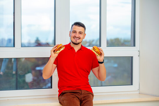 Young adult man with beard eating delicious fresh big burgers sitting on the window