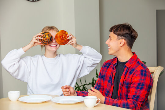 Young beautiful happy couple guy and girl eating sweet buns for Breakfast at the table
