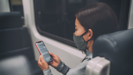 Coronavirus lifestyle bus passenger using mobile phone during commute at night during curfew and lockdown. Woman texting online on contact tracing app while wearing face mask.
