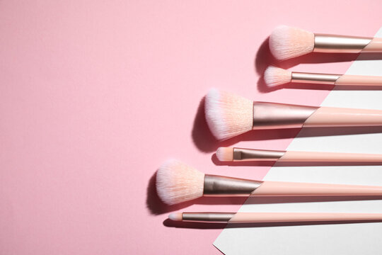 Flat lay composition with professional makeup brushes on color background. Space for text