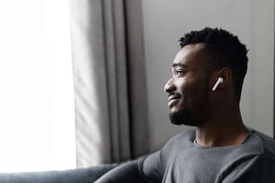 Close-up side view on handsome African-American guy with an airpods earphones spends time at home, listening music