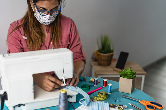 Mature woman working with sewing machine doing homemade face mask for preventing and stop corona virus spreading - Textile seamstress and healthcare people concept