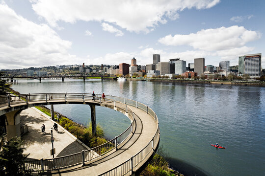Looking over the Eastbank Esplanade towards downtown Portland on a sunny day.  A handful of people are walking in the foreground and a kayaker rows by in the river.