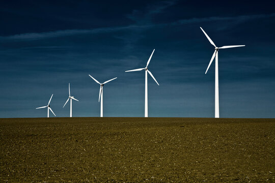 A row of windmills stand tall against a deep, dark blue sky.