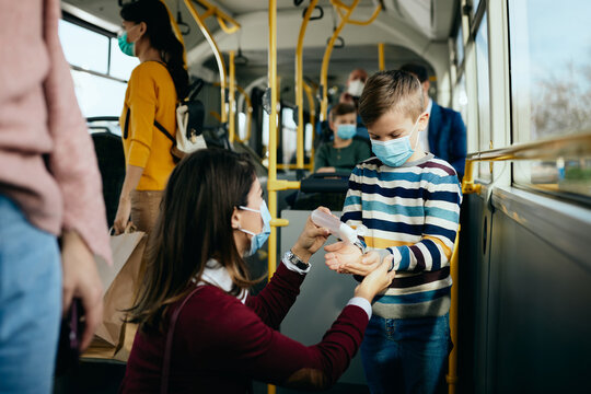 Small boy disinfecting hands while commuting in a bus with his mother during coronavirus pandemic..