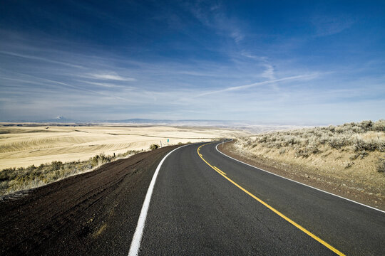 A single lane highway curves around a very low hill in the high desert of Eastern Oregon.  A dry, arid landscape stretches on for miles in the distance.