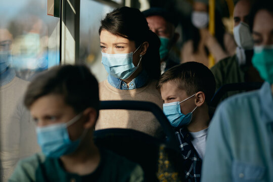 Mother and son wearing face masks while traveling by public transport.