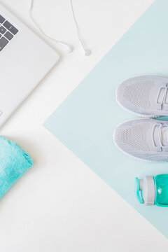 Home online workout concept. Flat lay sport shoes, new sneakers, laptop on a light background