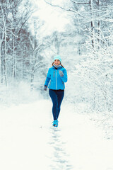 Fototapeta Woman jogging towards camera in cold and snowy forest