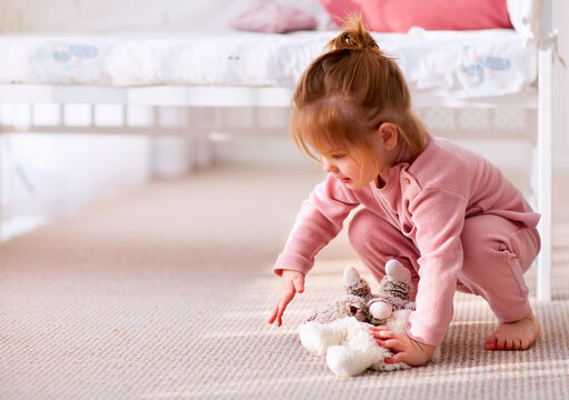 cute baby girl playing toys on the carpet in nursery room at home