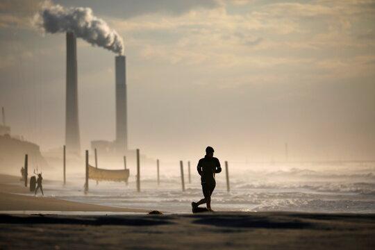 A man runs on a beach during a third national COVID-19 lockdown in Ashkelon