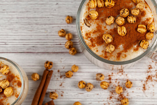 Flat lay image of two glass cups of traditional Turkish Boza, a sweet and sour fermented drink based on wheat and corn. It is served with leblebi chickpeas and cinnamon in winter months.