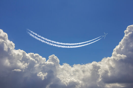 Airplane flies above white clouds in a deep blue sky and leaving jet trail in the shape of smile