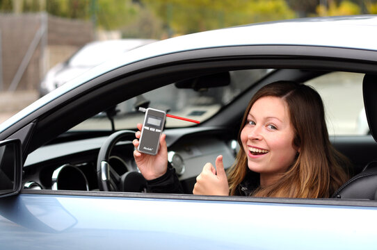 drink and drive young female driver being subject to test for alcohol content with use of breathalyzer. she is smiling as she does not drive and drink