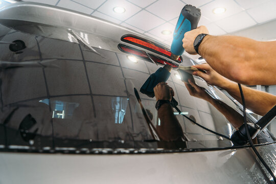 Car window tinting. Process of Installation window tint in Car Detailing Studio Garage by professional detailer.