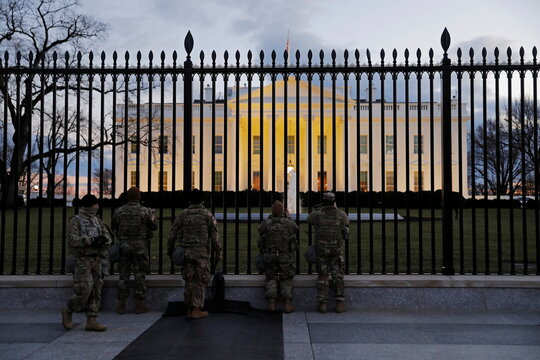 Members of the military look at the White House two days prior to U.S. President-elect Joe Biden's inauguration, in Washington