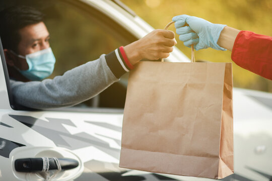 Masked man, restaurant customer, in car to pick up food on Christmas Day Online food delivery concept