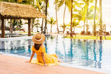 Fototapeta Young woman traveler relaxing and enjoying the sunset by a tropical resort pool while traveling for summer vacation